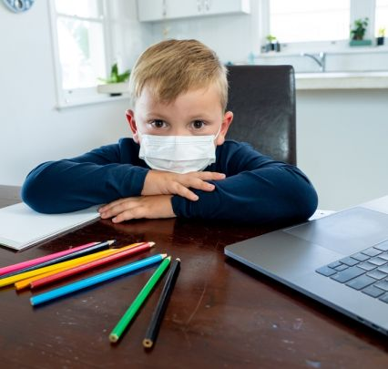 Child at laptop with mask